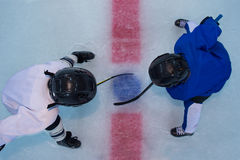 Hockey players on face off. Two young hockey players stands on red line in face off. Top view Royalty Free Stock Photos