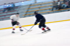 Hockey Players On the Ice. Abstract motion blur of two hockey players skating down the ice rink Royalty Free Stock Photo