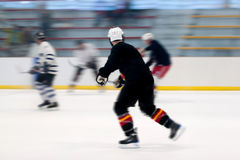 Hockey Players On the Ice. Panned motion blur of two hockey players skating down the ice rink Royalty Free Stock Images