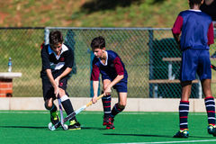 Hockey Players Schools Playing Astro. Hockey Players in action male teenagers challenge for possession of the ball at the under sixteen years age group game stock images