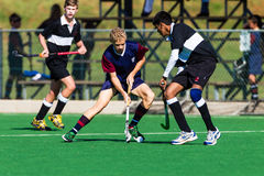 Hockey Players Teenagers Playing Astro. Hockey Players in action male teenagers challenge for possession of the ball at the under sixteen years age group game royalty free stock photography
