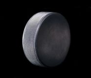 Hockey puck. Sideview of hockey puck on black background Stock Photo