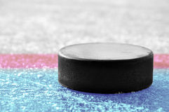Hockey puck. Black hockey puck on ice rink Stock Photos