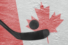 Hockey puck with a black stick and Canadian flag Stock Images