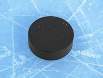 Hockey puck on blue ice on hockey rink. Surface Royalty Free Stock Photo