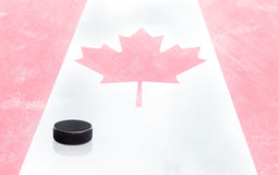 Hockey Puck and Canadian Flag on Ice With Copy Space Royalty Free Stock Images