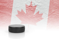 Hockey puck and a Canadian flag Stock Photos