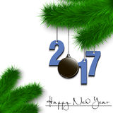 Hockey puck and 2017 on a Christmas tree branch. Happy New Year and numbers 2017 and hockey puck as a Christmas decorations hanging on a Christmas tree branch on Stock Image