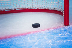 Hockey puck crossing goal line. Hockey puck crossing red goal line. Close view stock images