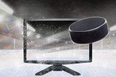 Hockey Puck Flying Out of TV Screen in Stadium Stock Photo