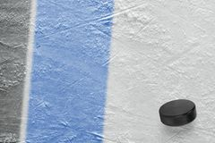 Hockey puck and fragment of the ice arena with black and blue lines. Puck on ice hockey arena. Concept, hockey, wallpaper stock photo