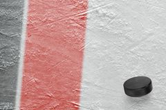 Hockey puck and fragment of the ice arena with black and red lines. Puck on ice hockey arena. Concept, hockey, wallpaper royalty free stock photos
