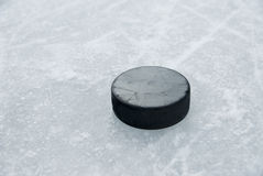 Hockey puck on ice. Black hockey puck on ice Royalty Free Stock Image