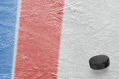Hockey puck and ice arena fragment with blue and red lines. Puck on ice hockey arena. Concept, hockey, wallpaper stock photos