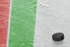 Hockey puck and ice arena fragment with red and green lines. Puck on ice hockey arena. Concept, hockey, wallpaper royalty free stock photography