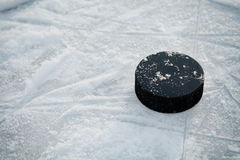 Hockey puck on ice hockey rink Stock Photos