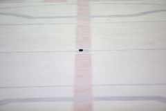 Hockey puck on ice Stock Images