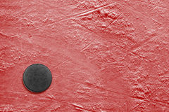 Hockey puck on ice red Stock Image