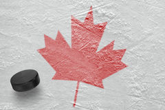 Hockey puck and maple leaf Royalty Free Stock Photos