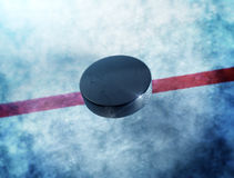 Hockey Puck Middle. Hockey puck above the ice and red line with lens flare around puck Stock Image