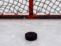 Hockey puck in net Royalty Free Stock Photography