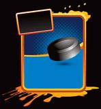 Hockey puck on orange splattered advertisement Royalty Free Stock Image