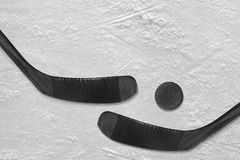 Hockey puck and a pair of black sticks on the ice Stock Photo