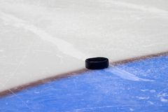 Hockey puck stand on side on goal line. Close view royalty free stock images