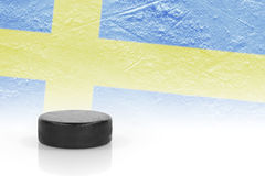 Hockey puck and a Swedish flag Royalty Free Stock Photos