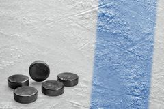 Hockey pucks and a fragment of the ice arena with a blue line. Puck, blue line and background hockey arena. Concept, hockey, background stock photo