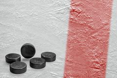 Hockey pucks and a fragment of the ice arena with a red line. Washers, red line and background hockey arena. Concept, hockey, background royalty free stock photo