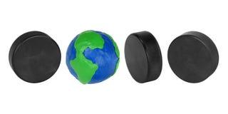 Hockey pucks and plasticine globe. Plasticine globe and hockey puck on a white background Royalty Free Stock Photography