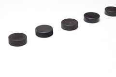 Hockey Pucks. A series of hockey pucks with one in sharp focus Royalty Free Stock Images