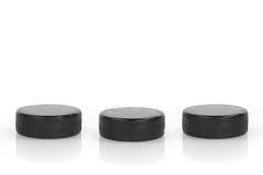 Hockey Pucks. Three hockey pucks in a row on a white background. Concept Stock Photos