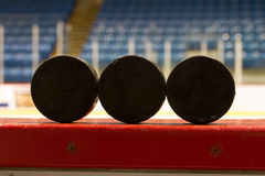Hockey Pucks. Three (3) hockey pucks sit on the side of the rinkboards in this Canadian hockey arena/rink Royalty Free Stock Images