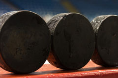 Moisture Hockey Pucks. 3 hockey pucks sit on the side of the boards while a practice takes place Royalty Free Stock Photo