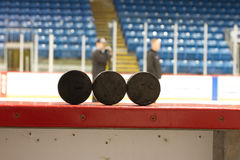 Hockey Pucks with players. Three (3) hockey pucks sit on the side of the rinkboards in this Canadian hockey arena/rink while two individuals in the background Royalty Free Stock Photography