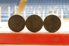 Hockey Pucks. Three (3) hockey pucks sit on the side of the rinkboards in this Canadian hockey arena/rink while two individuals in the background skate Royalty Free Stock Images