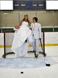 Hockey Romance. A bride and groom on hockey net in an ice rink Stock Photography