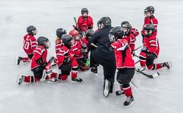 Hockey-Saison, Kinder spielen nationales Spiel an einem Winterkarneval lizenzfreies stockbild