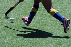 Hockey shadow 2. A field hockey player runs with the ball and stick Stock Photo