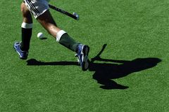 Hockey shadows. A field hockey player runs with the ball and stick Stock Image