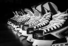 Hockey skates lined up in locker room Royalty Free Stock Images