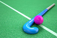 Hockey Stick And Ball. A 3D rendering of a hockey stick and ball on green astroturf in the daytime Royalty Free Stock Photos