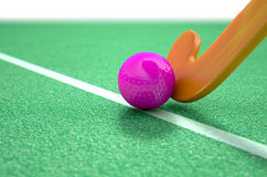 Hockey Stick And Ball. A 3D rendering of a hockey stick and ball on green astroturf in the daytime Stock Photography