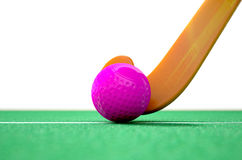Hockey Stick And Ball. A 3D rendering of a hockey stick and ball on green astroturf in the daytime Stock Photo