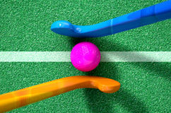 Hockey Stick And Ball. A 3D rendering of two hockey sticks stadning opposite each other over a ball on green astroturf in the daytime Stock Image