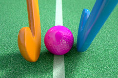 Hockey Stick And Ball. A 3D rendering of two hockey sticks stadning opposite each other over a ball on green astroturf in the daytime Stock Photos