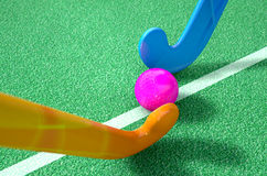 Hockey Stick And Ball. A 3D rendering of two hockey sticks stadning opposite each other over a ball on green astroturf in the daytime Stock Photo