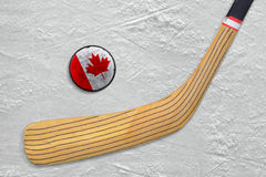 Hockey stick and puck on the Canadian hockey rink Royalty Free Stock Photo